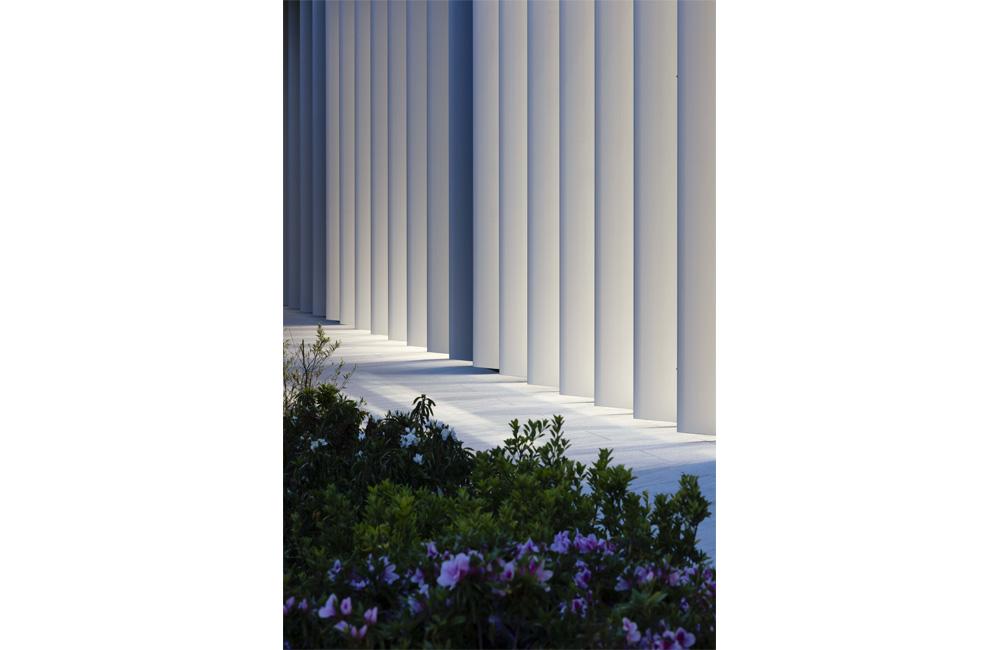 室内の灯りが外装アルミルーバー材に反射する夜間景観。高品質、高付加価値を表象した新本社ファサード。品のある柔らかな空間が演出される。
