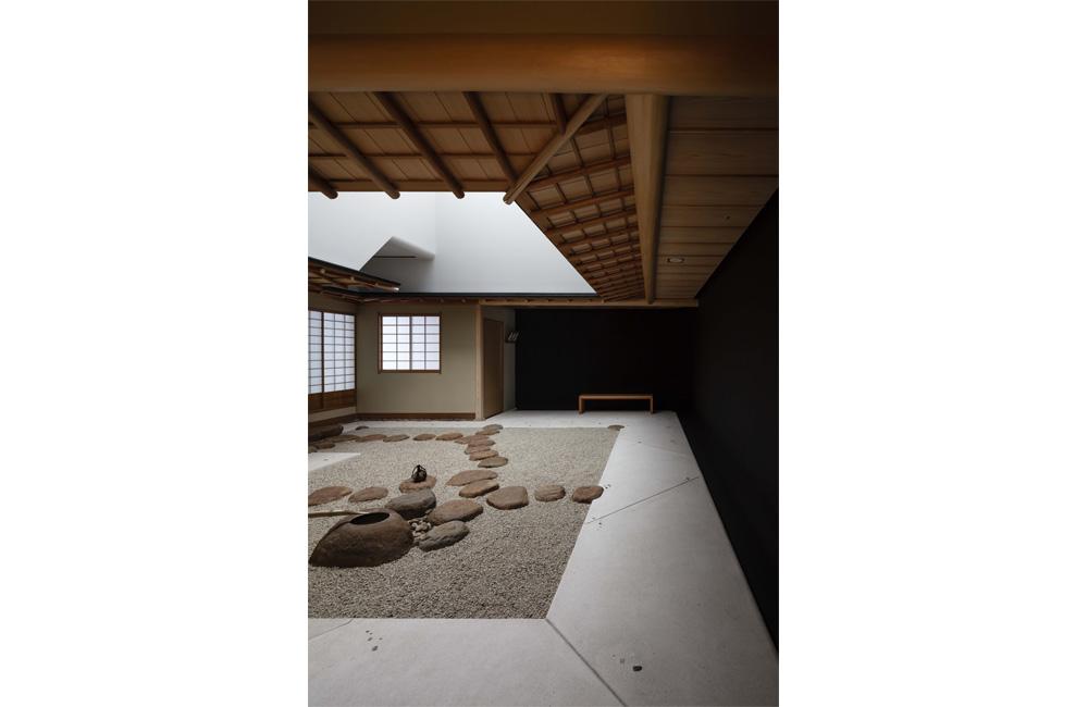 茶室露地空間。茶室の平面は以前のままで、手水鉢と飛び石は再配置し、右側の黒漆喰壁や一二三石が埋め込まれた土間は新たに計画された。黒漆喰壁の足元、壁上部やトップライトの角にはRを付け、エッジが見えない工夫がなされている。