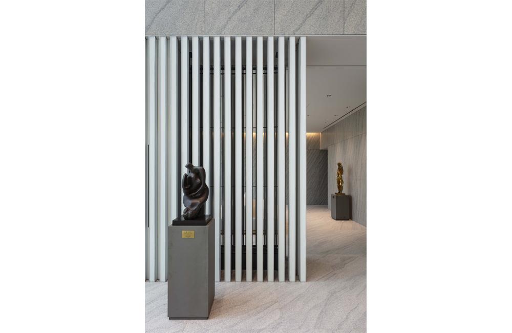 エントランスホールと待合スペースとの間仕切りとなる縦ルーバーの内側にはボアホールによる地中熱を利用した冷温水式の放射冷暖房を設置。インテリアデザインはデンマークのNorm Architectsの協力による。