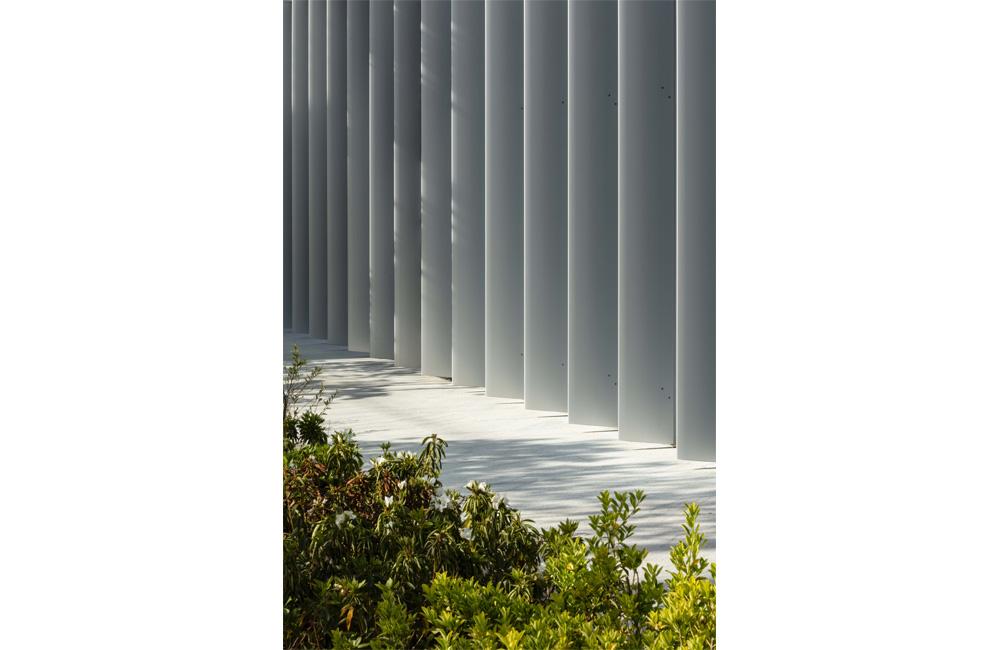 パッシブデザインの観点から採光と日射遮蔽を考慮した特注のアルミ押出材を配したファサード構成。